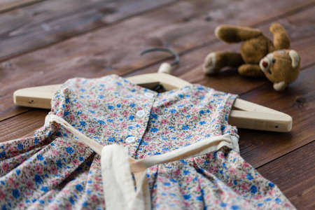 Child dress on hanger on wooden floor background
