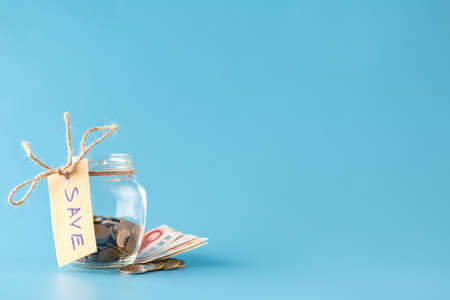 Coins in savings jar full of money Imagens