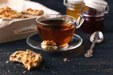 A cup of tea and basket with cookies served for breakfast on wooden table, dark background