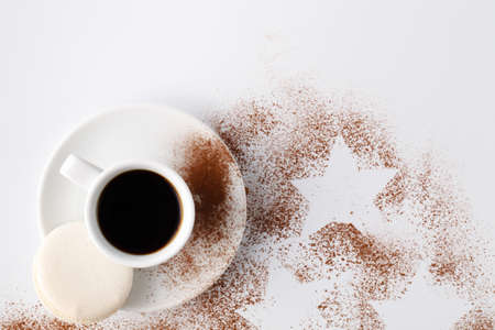 One small cup of cofee and cocoa powder on white table Stock Photo
