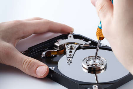 Hard disc drive disassembling close up. Repairman opening hdd for recovery information, service center and electronics repair concept