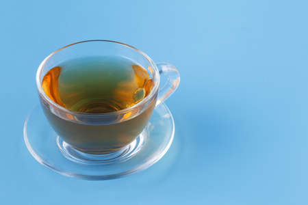 Glass cup with herbal tea on blue background Stock Photo