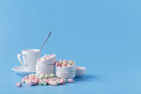 Small candy marshmallow in rosette on blue background Stock Photo