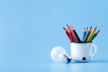 Heap of colour pencils and light bulb on blue background