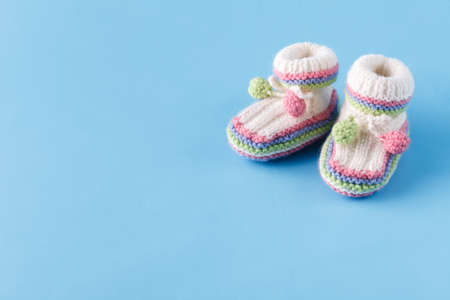 Newborn announcement Baby booties on blue with copy space