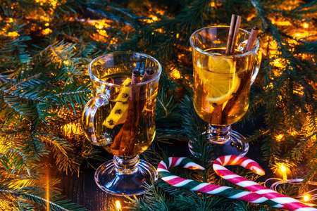 New Years mulled wine in a glass on the background of twigs, candles and garlands. Stock Photo