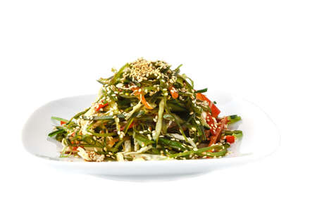 Close up portion of green wakame seaweed salad on white plate isolated on white background, low angle view Reklamní fotografie