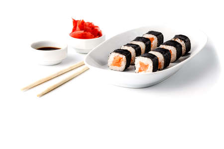 Traditional eastern dish with salmon sushi rolls on a white plate 写真素材