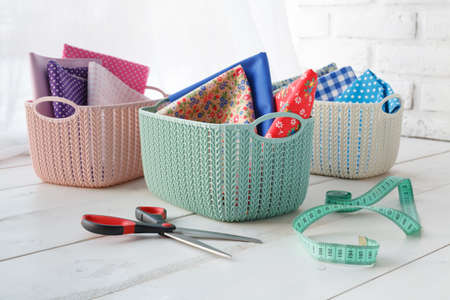 home organizers colored baskets on white table Archivio Fotografico