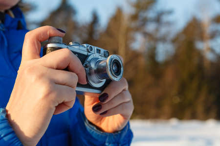 Vintage camera in hand, outdoor winter with sky