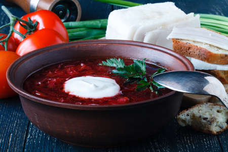 Borscht beetroot soup, on the table with slices of rye cereal bread and sour cream. Rustic style Stock Photo