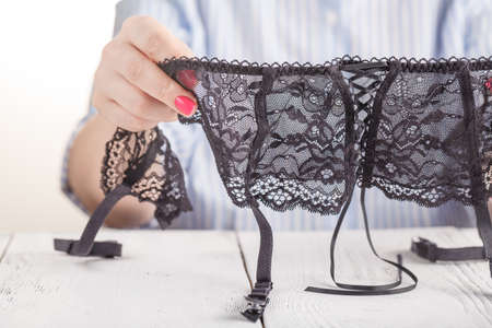 Black lace belt for stockings in female hand. Fashionable concept