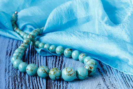 turquoise beads on blue wooden background