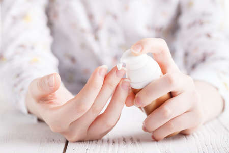 Female applying cream on her hand, closeup