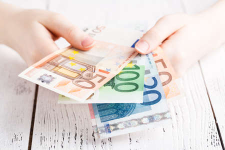 Close up female hands holding few euro banknotes