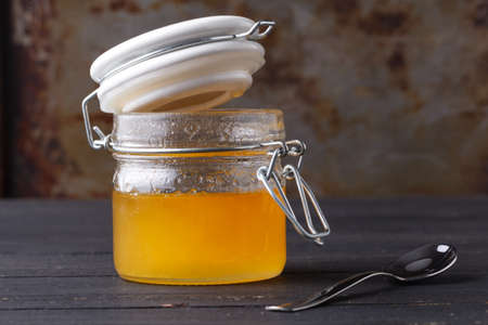 Golden honey in glass jar on rustic table