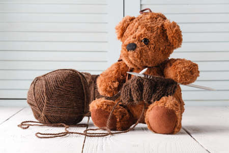 Knitting leisure, ball of wool and needle in hands of toy bear Imagens