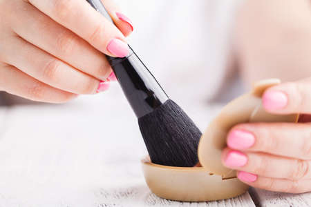 Close up of make-up brush with jar of loose cosmetic powder in hand
