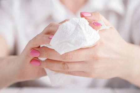 Woman cleaning her hands by using white tissue paper. Stock Photo
