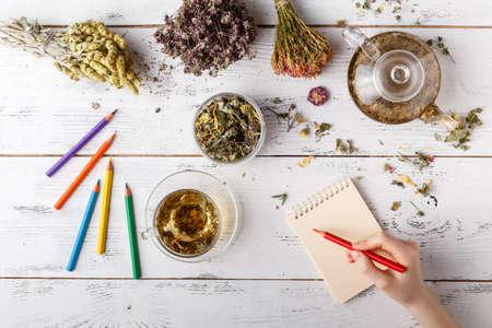 Happy woman with medicinal herbs brewing herbal tea