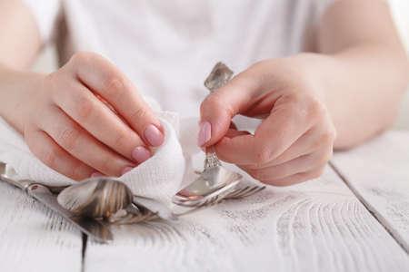 La donna sta pulendo e asciugando i cucchiai per la ristorazione.