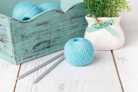Female leisure, box with knittng yarn on white table
