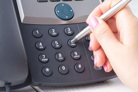One human hand pressing key on phone
