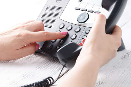Call center or office phone concept, female finger press number on phonepad Stock Photo