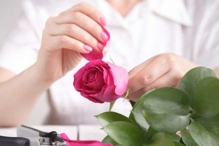 Female florist make bouqet on table^ working prosess