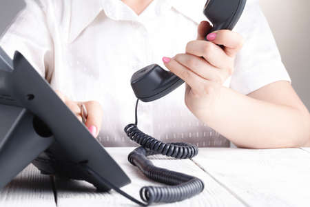 Female hand holding phone receiver and dialing number Stock Photo