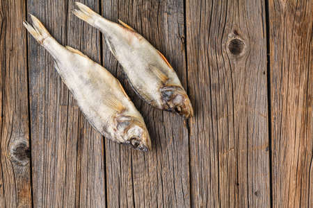 Close-up dried fish on a dark rustic wooden background Stock fotó