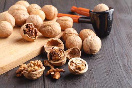 Walnuts and nutcracker on wood Stock Photo