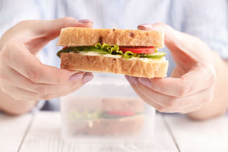 food, dinner and people concept - woman eating salmon panini sandwich with tomatoes and cheese at workplace Stock Photo