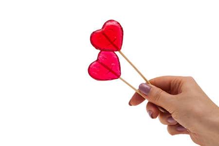 sweet heart shaped lollipops in hand, isolate Banco de Imagens