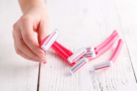 Pink female razors in hands on the white background. Set of razors on white background. Pink women's disposable razors