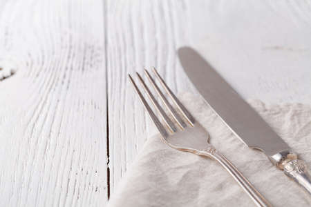 Knife, fork with linen serviette on the white
