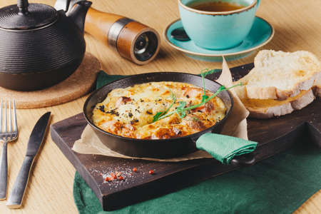 Omelet with vegetables and cheese. Frittata in a frying pan^ breakfast set