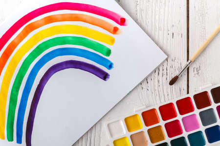 Painting of rainbow on notebook or sketch book with paintbrush on wooden planks for background Stok Fotoğraf
