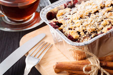 Traditional Christmas cake with dried fruits, raisins and a cup of tea on a wooden table with Christmas decorations Archivio Fotografico