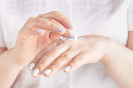 Closeup shot of woman hands applying moisturizing hand cream Stok Fotoğraf