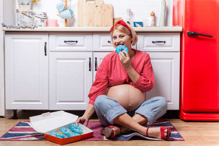 pregnant woman with belly holding donut. The concept weight control and an unhealthy diet during pregnancy Stock Photo