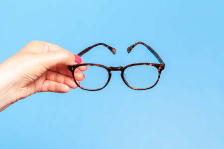 Woman hand holding spectacles on blue background