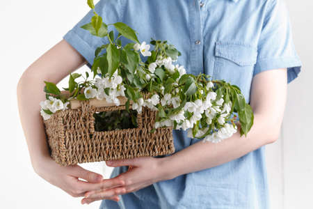Hipster Girl in rustic linen dress holding big apple tree flowers in wicker basket on white background 版權商用圖片