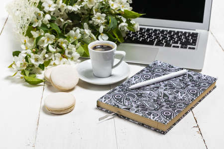 Work space with a laptop, a cup of tea and flowers on the wooden background. Home office composition, freelance concept Stock Photo