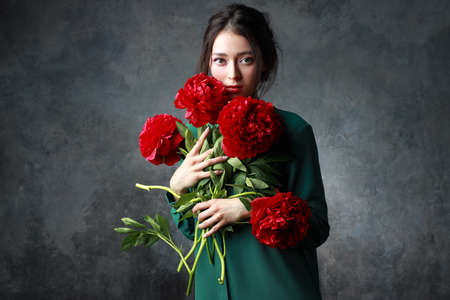 Beautiful girl in tender green dress with bouquet flowers peonies in hands. Playful fashion model looking at camera