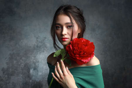 Gorgeous young woman with bright make-up posing with peony flowers. Stock Photo
