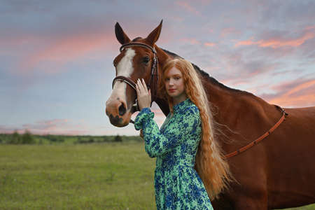 Woman with her horse at sunset, autumn