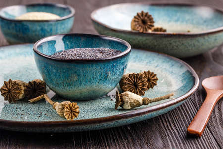 Poppy seeds and seedpods in ceramic bowl Banco de Imagens