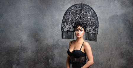 Young sexy woman brunette in stylish neofolk black kokoshnik stands on stone backgrount