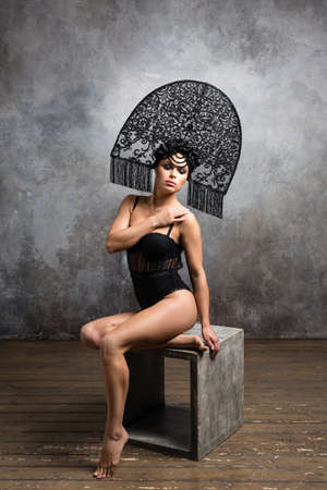 beautiful young girl in lace bodysuit and fashionable kokoshnik on a background of gray wall